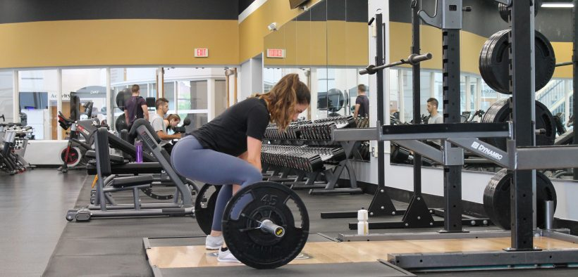 How to master the squat rack. Woman squatting in front of squat rack holding a barbell.