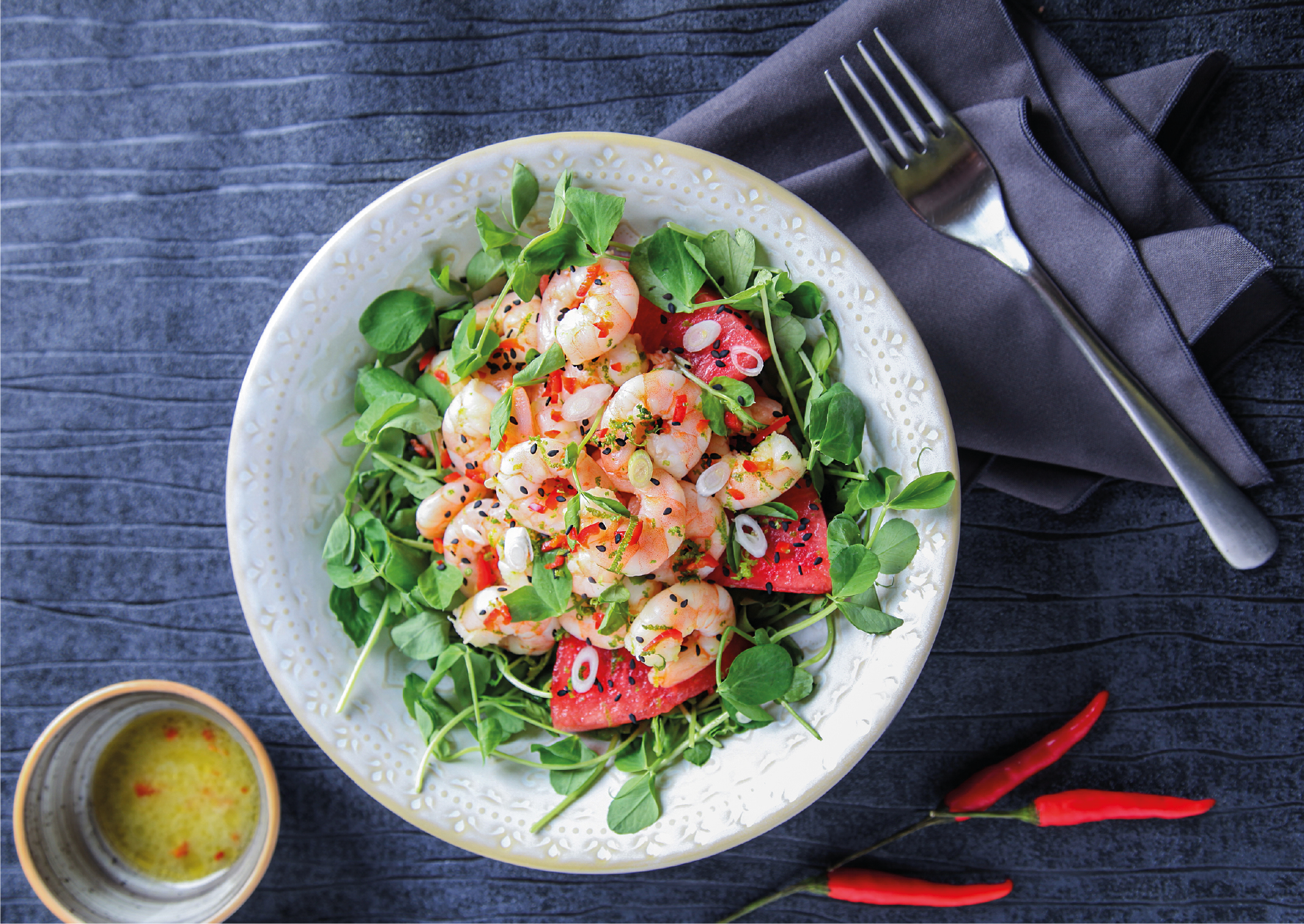 dish with green leafy salad and watermelon, topped with peeled cooked king prawns and sesame seeds. On the side there is a fork on a grey napkin, chilli peppers and olive oil dressing.